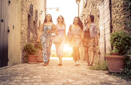 Grupo de muchachas que caminan en un centro histórico en Italia. Gente feliz con el buen humor que toman una excursión