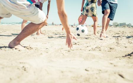 Groep vrienden met plezier op het strand voetballen. gelukkige mensen en spelletjes op het strand concept van