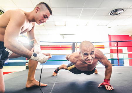 handed: Muay thai fighter doing push ups  - Coach training his athlete for a boxe match - Sportive men working out in a martial arts gym