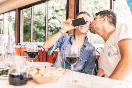 restaurant dining: Couple photographing food at restaurant - Romantic date in a italian restaurant, woman taking selfie Stock Photo
