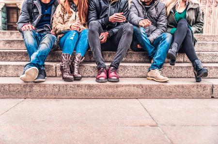Grupa ludzi siedzi na schodach na zewnątrz, z bliska na niskim korpusie sekcji - wielorasowe znajomych rozmowy i zabawę na spotkanie w plenerze Zdjęcie Seryjne
