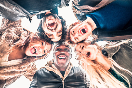 integrated group: Multi-ethnic group of friends in circle - Several people of diverse ethnics smiling and looking down at camera - Concepts about friendship, teamwork, immigration and unity Stock Photo