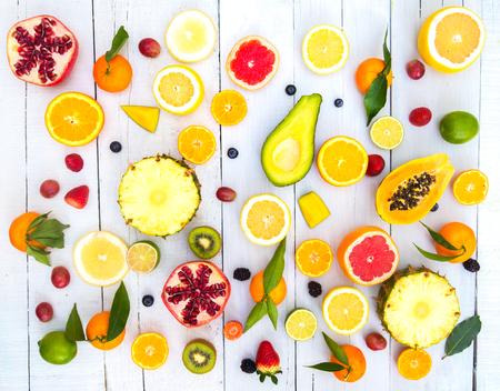 Mix aus farbigen Früchten auf weißem Holz Hintergrund - Zusammensetzung der tropischen und mediterranen Früchten - Konzepte über Dekoration, gesunde Ernährung und Lebensmittel Hintergrund