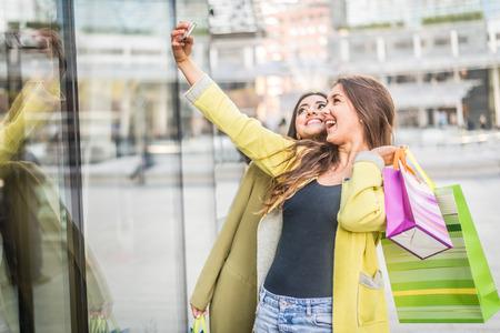 chicas de compras: Dos mujeres muy jóvenes takinga autofotos mientras compras - Chicas comprar algo de ropa en un centro comercial y que se divierte