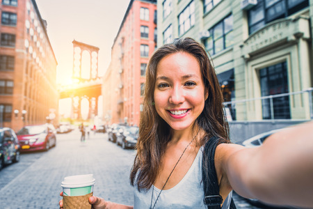 Pretty mixed race woman taking a selfie in New York, Brooklyn Bridge in the background - Beautiful girl walking on the streets of NY and photographing some landmarks Archivio Fotografico