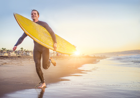 swimsuite: Surfer running on the beach