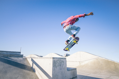 skateboard shoes: Skateboarder doing a trick in a skate park