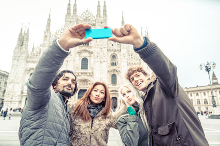 four people: Multi-ethnic group of friends taking a selfie in front of a famous landmark - Tourists photographing the Duomo cathedral in Milan - Four people on vacation sightseeing the city