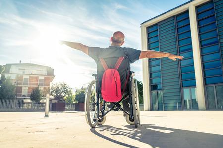 homem inválido sentado em uma cadeira de rodas e desfrutar de um passeio ao ar livre