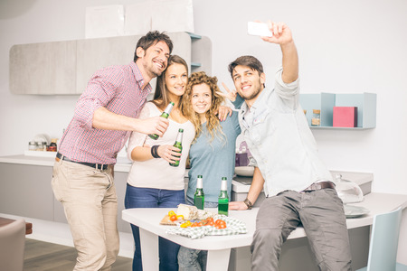 Four friends taking a selfie - Group of people celebrating at home and having fun Stock Photo