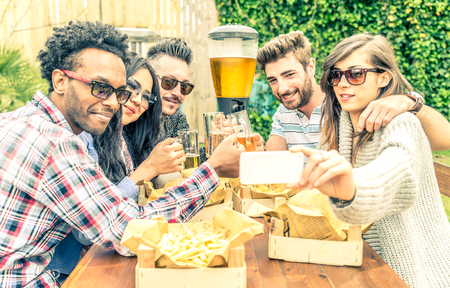 black couple: Multiracial group of friendstaking a selfie while eating in a restaurant - People toasting beer glasses on a barbecue party