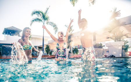 party friends: Friends having party and dancing in a swimming pool - Young people enjoying vacation in a tropical resort hotel Stock Photo