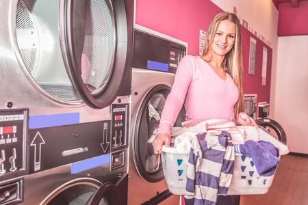 dirty clothes: Woman carrying a basket of dirty clothes in a self service washing centre Stock Photo