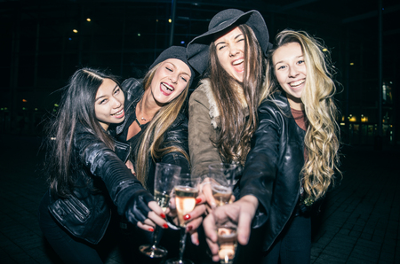 Pretty donne tostatura bicchieri di champagne e divertirsi - Quattro ragazze bere vino bianco frizzante e celebrare prima di andare in centro