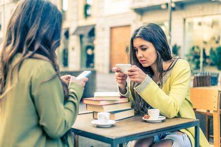 두 여자 술집에 앉아 휴대 전화를 쳐다보고 - 휴대용 장치에서 온라인 비디오를 시청하는 여자 스톡 콘텐츠