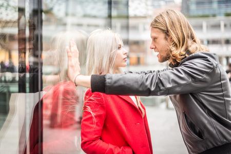 pareja enojada: Problemas de relación - Discusión de los pares al aire libre - Stalker, atacar a una mujer hermosa Foto de archivo