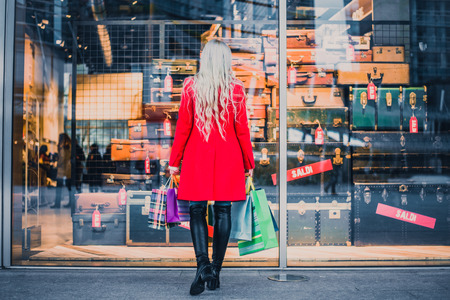 Donna che esamina vetrina - Piuttosto giovane ragazza in piedi di fronte a una boutique tenendo sacchi di shopping Archivio Fotografico
