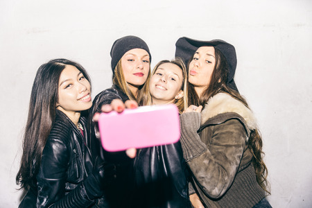 ethnics: Group of fashionable girls taking selfie and having fun - Women of diverse ethnics taking a self portrait picture