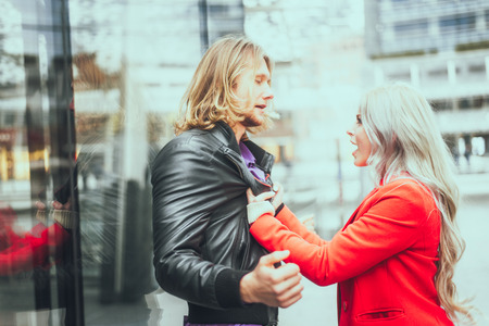 ex wife: Relationship issues - Woman grabbing her boyfriend and shouting out loud - Girlfriends pushing her man and he tries to exculpate Stock Photo