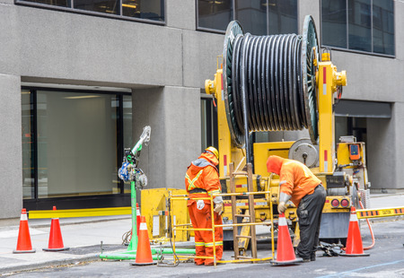 jack tar: Builder worker with pneumatic hammer drill equipment breaking asphalt at road construction site - Two workers draining sewer on the streets Stock Photo