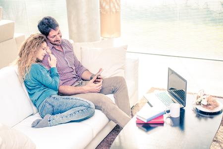 amadores: Pareja de amantes en casa viendo el smartphone en el sofá - El hombre y la mujer de relax del sofá, mujer que se inclina la cabeza sobre el hombro de su novio