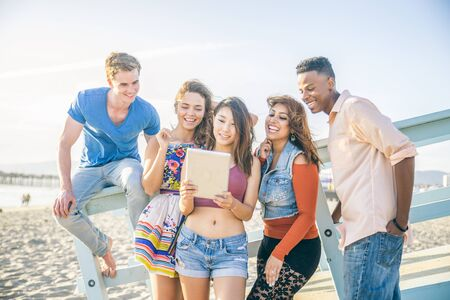 ethnics: Multi-ethnic group of friends watching tablet on the beach - Five persons of diverse ethnics having fun with modern technology