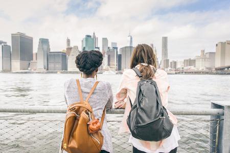 lesbianas: Dos mujeres que miran horizonte de Nueva York - multi�tnicas de la muchacha apoyado en una barandilla y mirando al paisaje urbano Foto de archivo