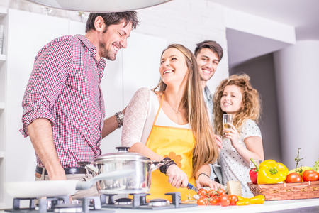 home cooking: Woman cooking at home and laughing with her friends - Home party, housewife preparing dinner for her guests Stock Photo