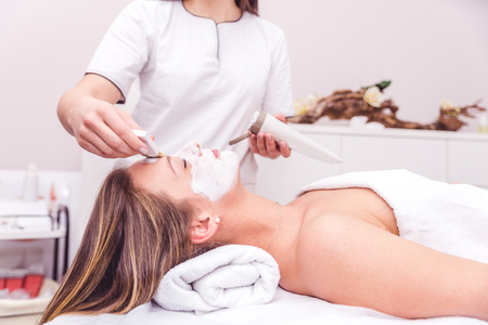 Beautician applying a beauty face mask to a woman lying down - Beauty skin treatment in a spa resort centre Stock Photo