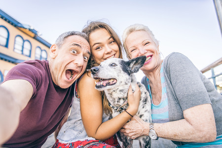 old people having fun: Self portrait of happy family with dog having fun outdoors - Grandparents and nephew taking a selfie Stock Photo