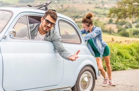 Engine break down.Strong young woman pushing a vintage car while man is emboldening her.Transportation, teamwork, funny concept