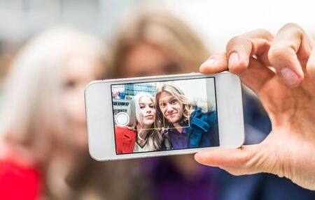 woman close up: Couple taking selfie with cellular phone - Two friends photographing themselves for a social network, close up on cellphone display