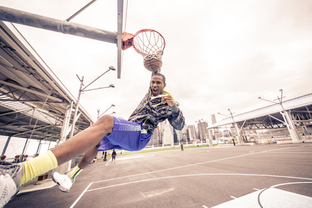Sportive man hanging from the basket and looking down triumphant at camera after a slam dunk - Basketball player scoring for his team