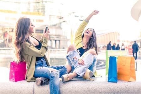 divercio n: Dos muchachas bonitas que se divierten mientras que las compras al aire libre - amigos Mejor hembra pasar tiempo juntos