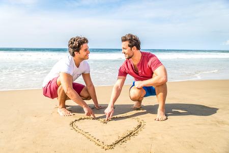 amor gay: Pareja gay dibujo un coraz�n en la arena - pareja homosexual de caminar en la playa en una cita rom�ntica