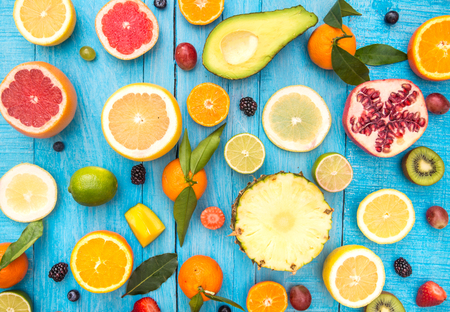 Mix of colored fruits on white wooden background - Composition of tropical and mediterranean fruits - Concepts about decoration, healthy eating and food background