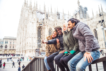 caucasian: Multiethnic group of friendstakinga selfie with smart phone to share on a social network - people of diverse ethnic having fun outdoors, Milans Duomo cathedral in the background Stock Photo