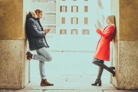 Couple regardant les téléphones portables et montrant désintérêt mutuelle - L'homme et la femme écrit sms sur les smartphones