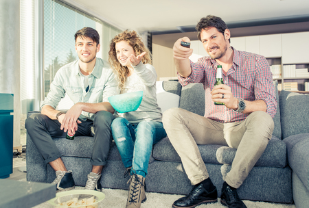 watching football: Group of friends watching television in the living room eating popcorns and drinking beer. Friendship and good mood concept
