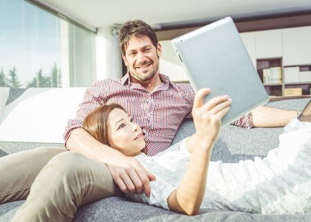 living things: Happy couple watching things on a digital tablet, at home in the living room