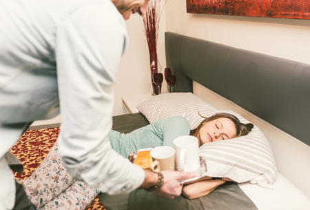 couple au lit: Beau petit ami apporter un petit-déjeuner à sa petite amie dans la matinée. Romance et de bonté dans la relation. Concept de l'amour et de la relation Banque d'images