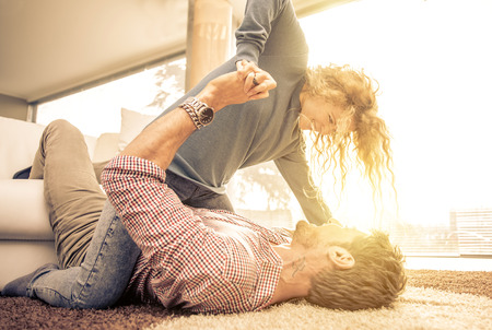 woman laying: Young couple playing on the carpet for fun in the living room
