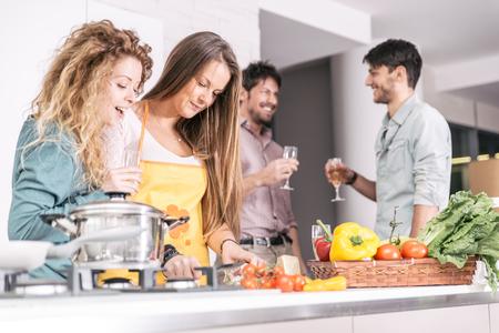 amateur: Grupo de amigos que cocinan en casa para cenar juntos. pasar tiempo con viejos amigos y compartir un buen estado de ánimo