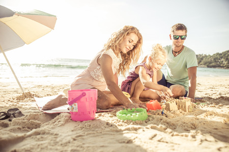 child swimsuit: Happy family playing on the beach and build some sand castle