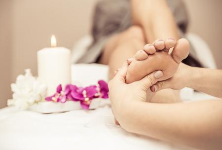 Cerca de los pies de la mujer y las decoraciones del salón de belleza. masaje de pies toma de esteticista. Concepto sobre el cuidado del cuerpo, spa y masajes Foto de archivo