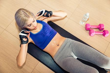 Hermosa mujer haciendo entrenamiento de abdominales en el piso. Mentir y tirar hacia arriba con ejercicio invertido abs