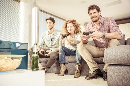 jugando videojuegos: Amigos jugando en la sala de estar y se divierten juntos Foto de archivo