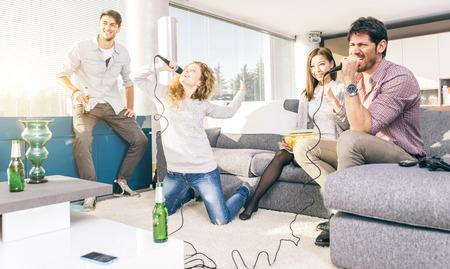Gruppo di amici che giocano karaoke a casa. Circa il concetto di amicizia, home entertainment e la gente