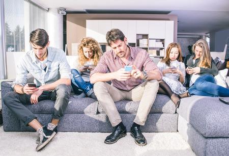 personas mirando: Los j�venes mirando hacia abajo en el tel�fono celular. Sentado en el sof� y haciendo caso omiso de los dem�s para centrarse en los tel�fonos inteligentes. Foto de archivo