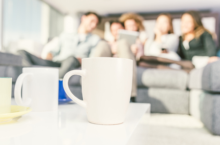 Close up on coffee cups in the living room with group of friends in the background Stock Photo
